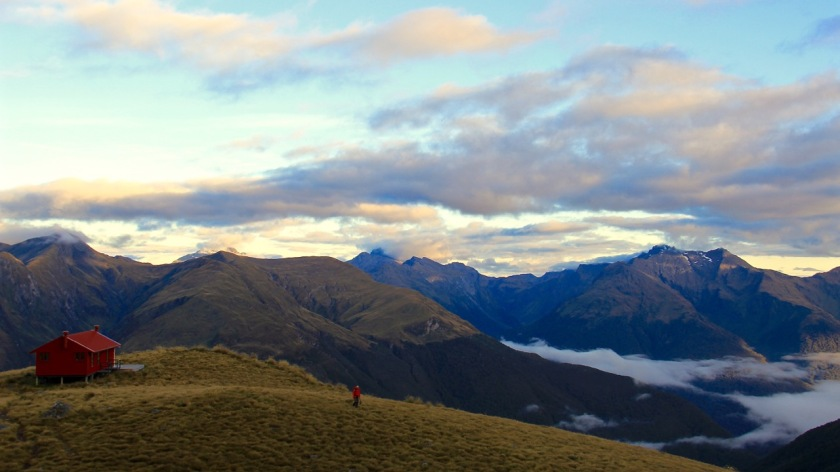 A hiker leaves Brewster Hut at sunrise, Mt Aspiring National Park NZ