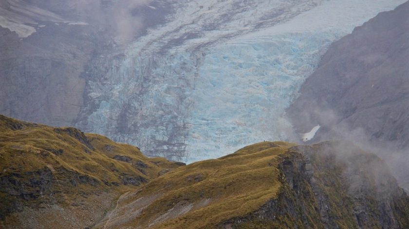 A hiker is dwarfed by the huge Dart Glacier on Cascade Saddle