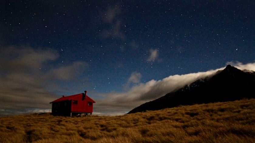 Brewster Hut and the stars of the night sky under moonlight