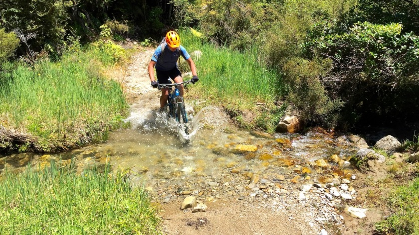 Mountain Biker crosses a creek on the Old Ghost Road, West Coast NZ