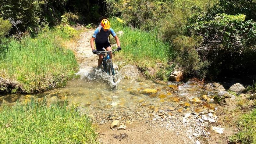 Mountain Biker crosses a creek on the Old Ghost Road, West Coast NZ