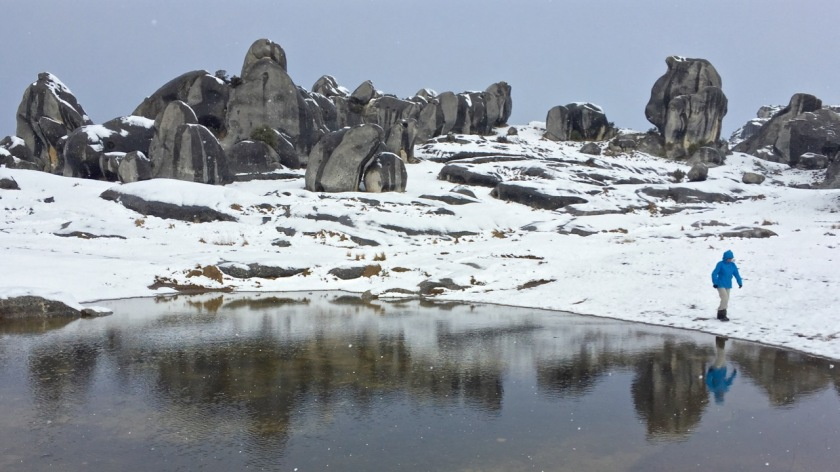 Castle Rocks covered in snow and reflected in a tarn