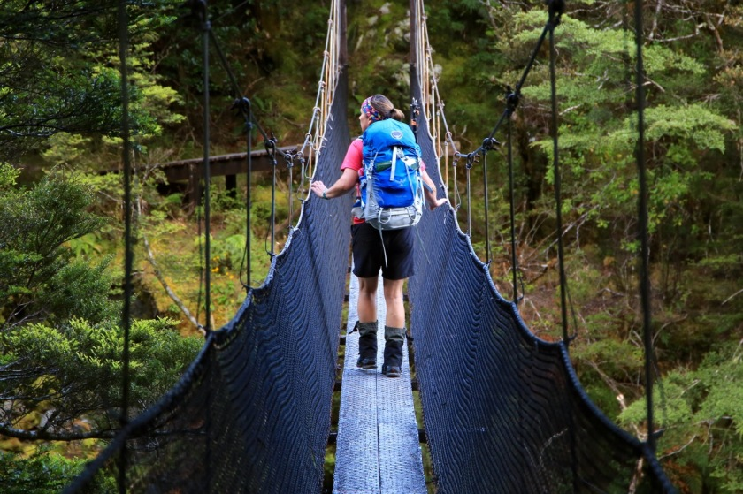 Hiker on a swing bridge in Mt Aspiring National Park NZ