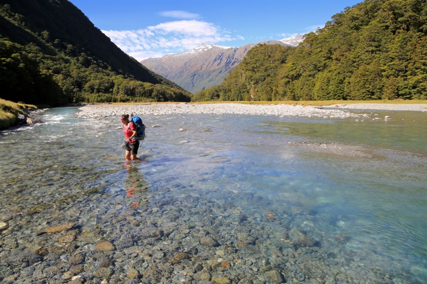 A hiker crosses a river in Mount Aspiring National Park, NZ