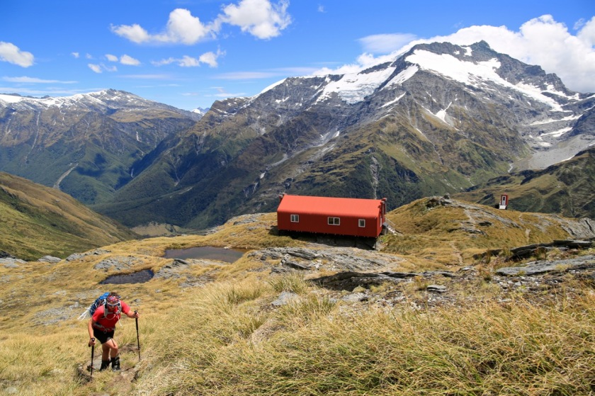 A hiker climbs above French Ridge Hut, Mount Aspiring National Park.