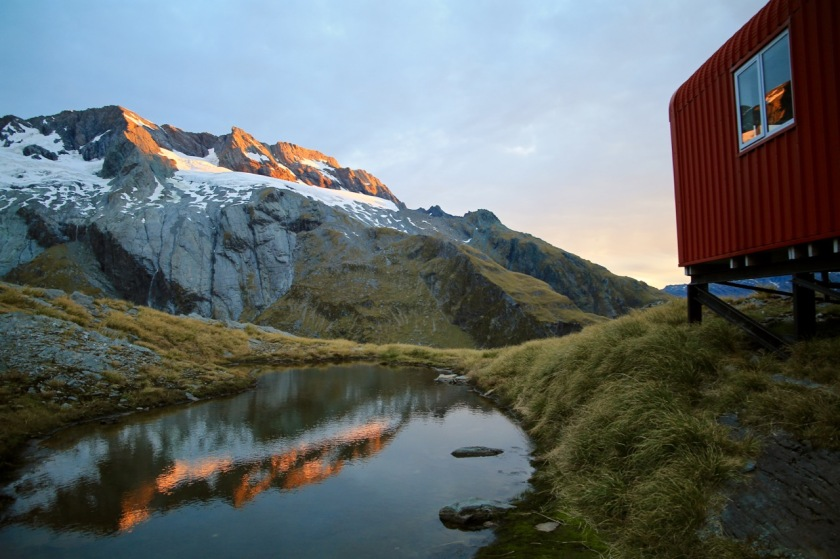 Mountain reflections in a small tarn at French Ridge Hut at sunset. Mt Aspiring National Park NZ