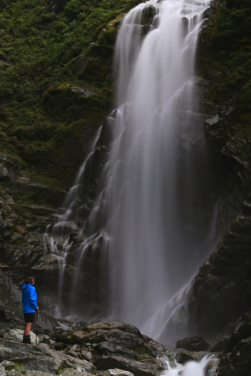 A hiker in front of a waterfall in Mount Aspiring National Park NZ