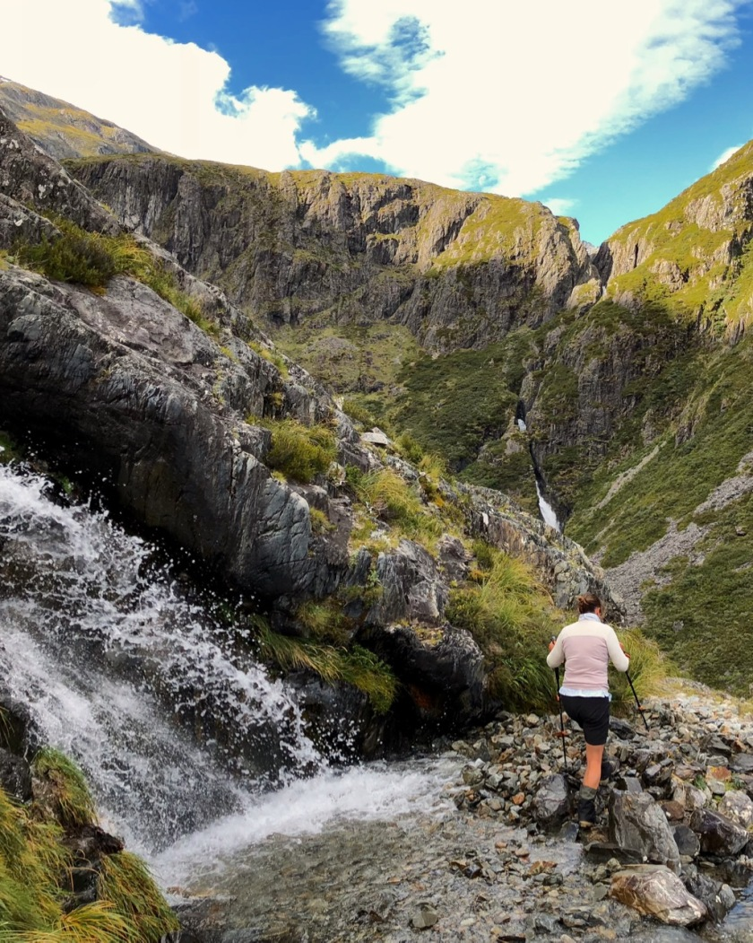 A hiker surrounded by waterfalls in the Southern Alps of New Zealand