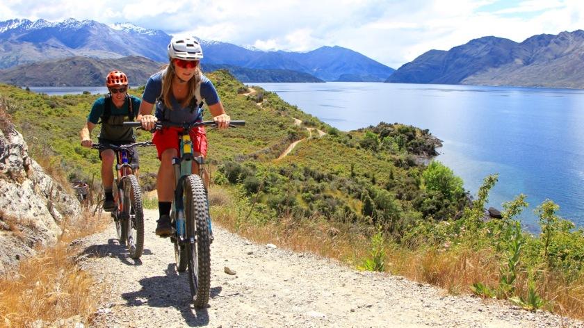 Mountain biking along a lakefront trail in Wanaka New Zealand