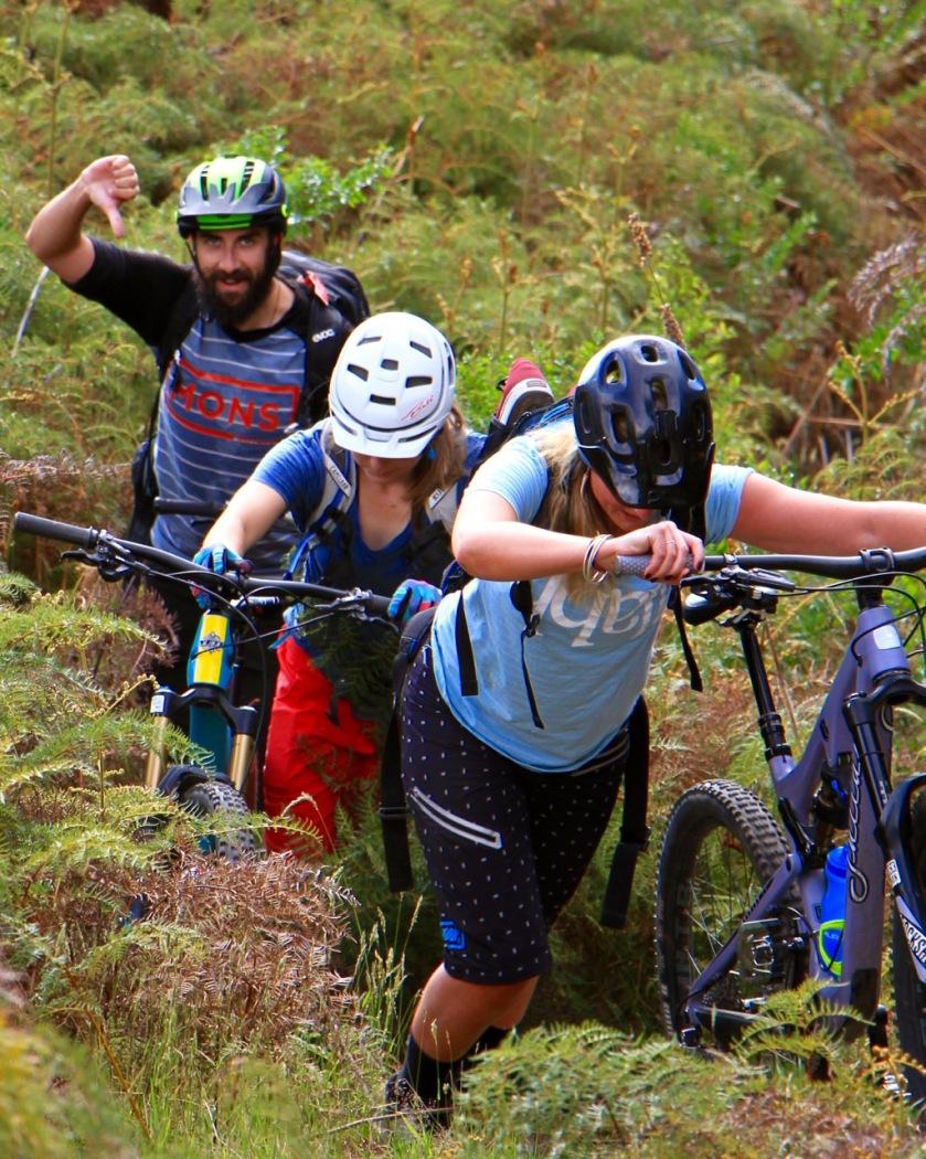 Mountain bikers pushing through dense bush in Lake Wanaka, NZ