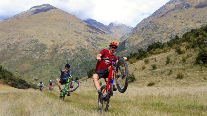 Mountain bikers wheelie in Wanaka, NZ