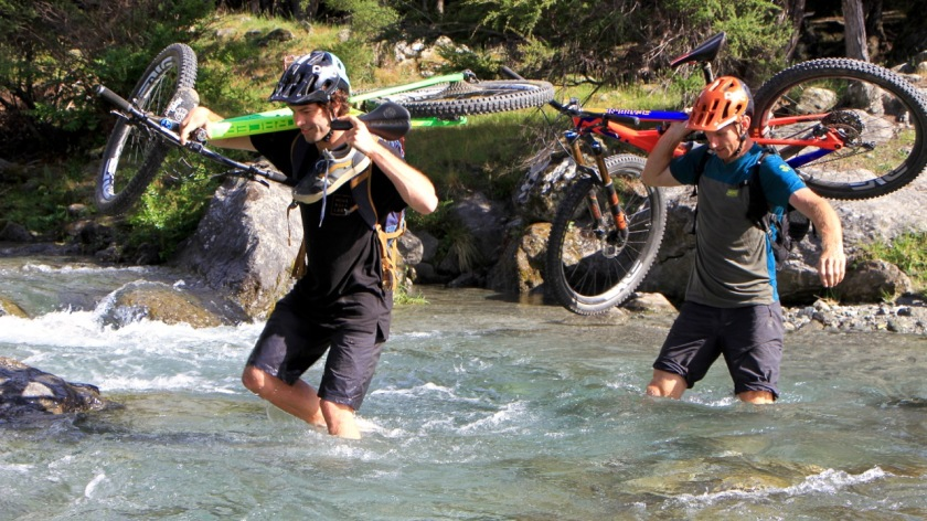 Mountain bikers cross a river, Lake Wanaka NZ