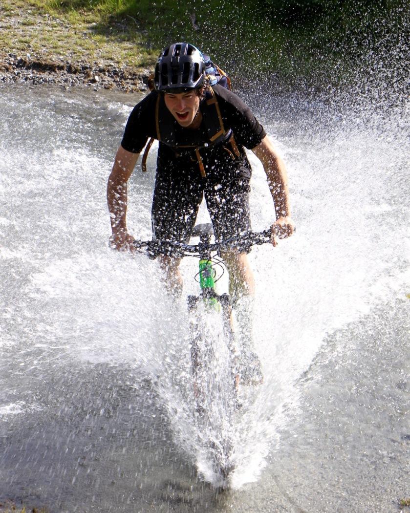 A mountain biker rides through a river, Lake Wanaka NZ