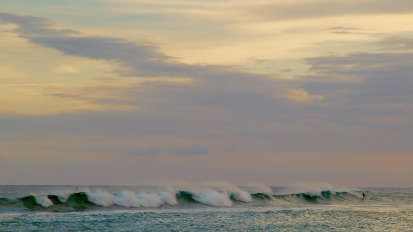 Surfing at sunset on Poipu Beach, Kaui, Hawaii