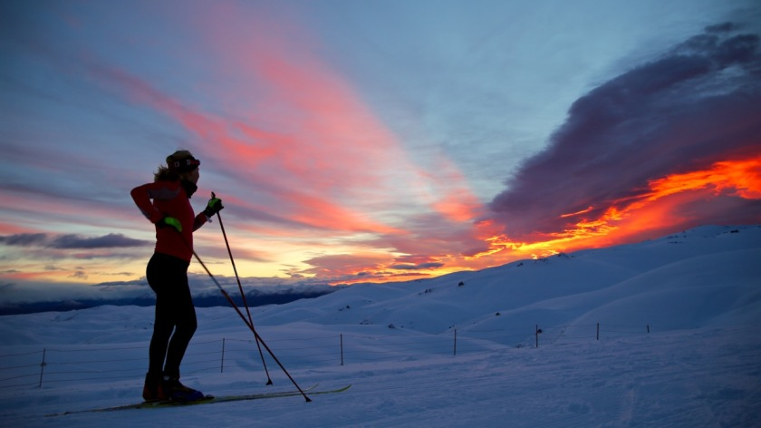 A cross country skier views the sunrise over the Southern Alps, Snow Farm, Wanaka NZ