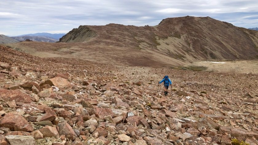 Hiking across scree slopes near Lake Ohau in the Southern Alps NZ