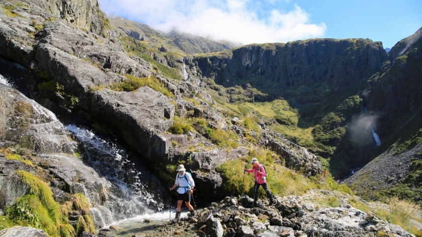 Hiking past waterfalls high in the mountains of the Southern Alps, New Zealand