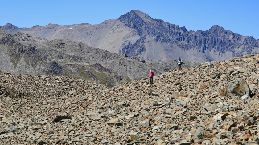 Hikers cross scree covered moraine walls in the Southern Alps, NZ