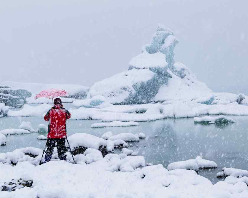 Photographer in a snow storm, Tasman Glacier Lake, Mt Cook, NZ