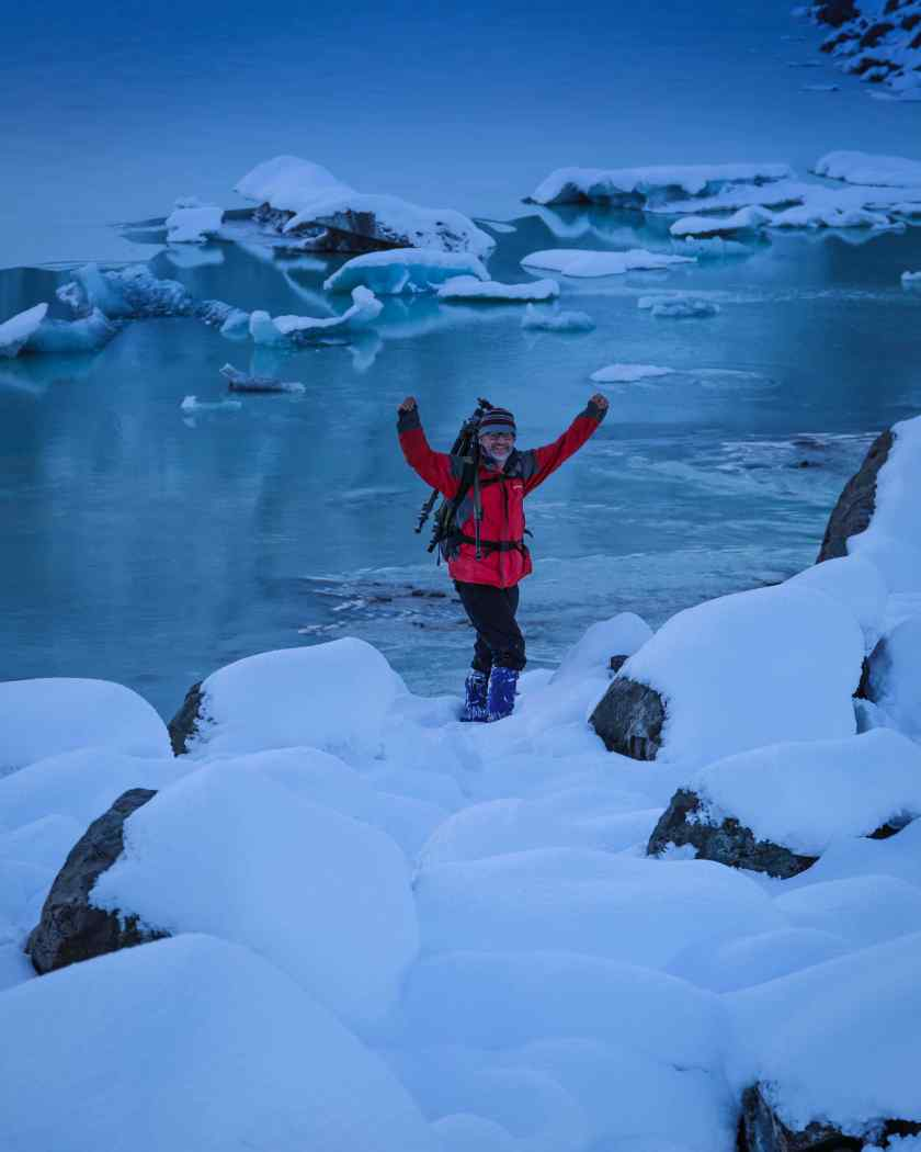 A photographer in snow at Tasman Glacier Lake, Mt Cook, NZ